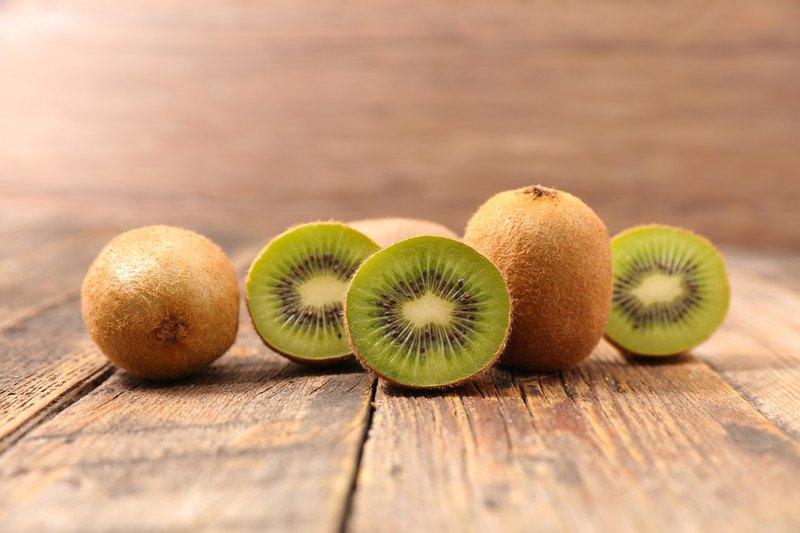 Three uncut kiwi fruit and three cut kiwi halves rest on a wooden table.
