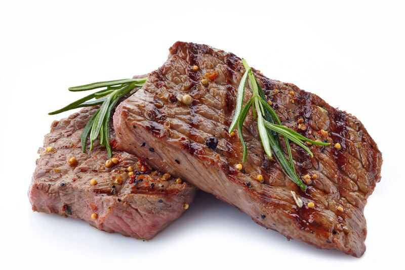 This photo shows two slices of cooked lean beef garnished with rosemary, against a white background.