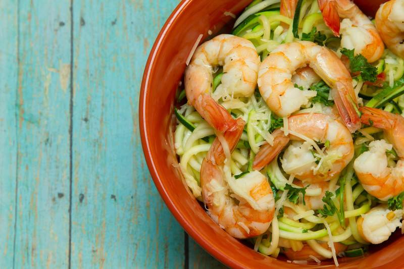 zucchini pasta with sauted shrimp in an orange bowl with blue wood background
