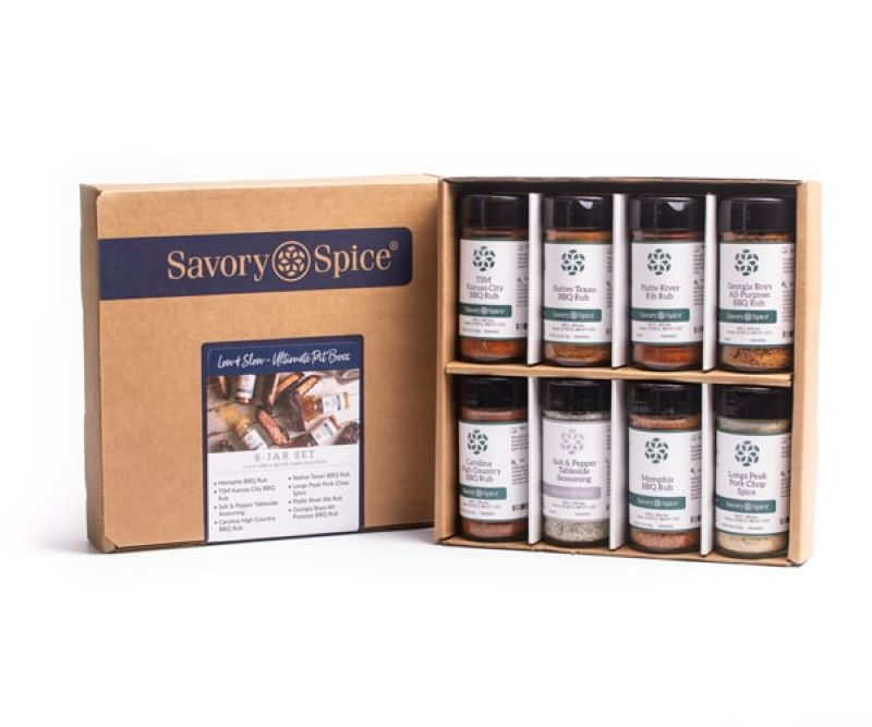 Savory Spice Box containing 8 jars of spices and rubs.  The cover of the box has the savory spice logo and sticker that says low & slow ultimate pit boss.