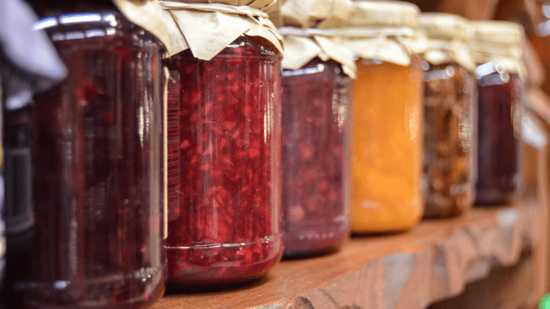 multicolored jars of jam on a wooden shelf