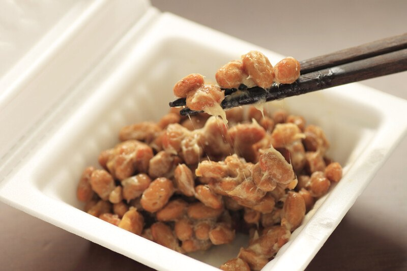 This photo shows two black chopsticks with natto on them hovering above an open white container of brown natto.
