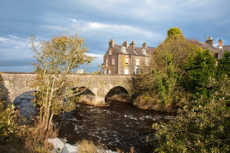 old bushmills irish whiskey distillery next to river with stone bridge