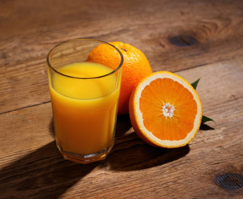 A whole orange and a half orange rest next to a glass of orange juice on a rough wooden background.