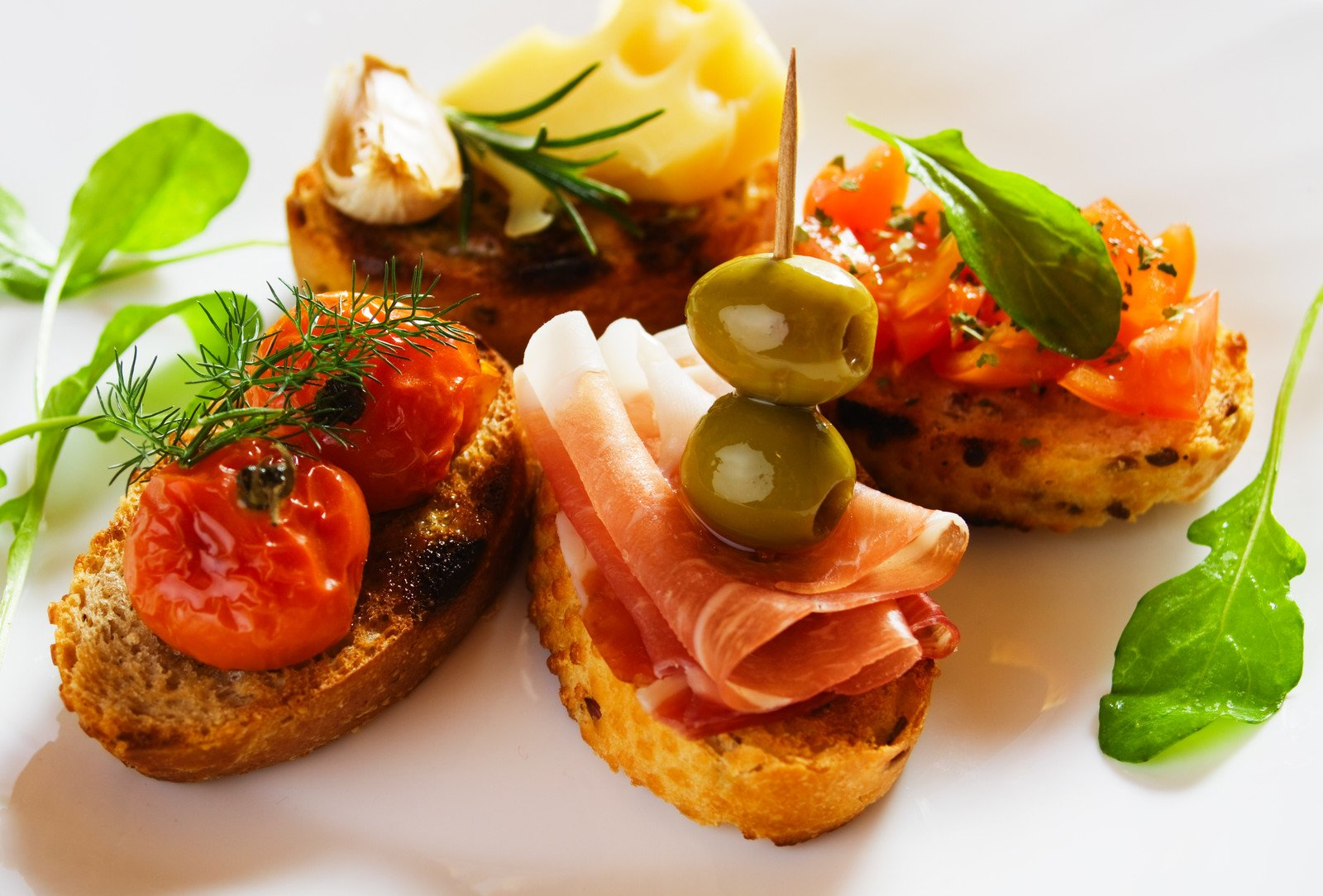 oven-toasted bruschette bread topped with slices of red smoked salmon olives and herbs
