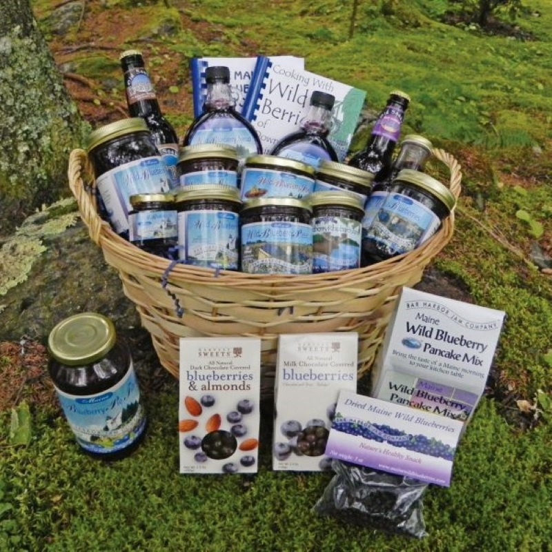 Large wicker basket displayed outside on green ground cover.  Contains an assortment of 21 different products including 9 jams, soda, syrup, cookbooks, candies, nuts, and baking mixes.
