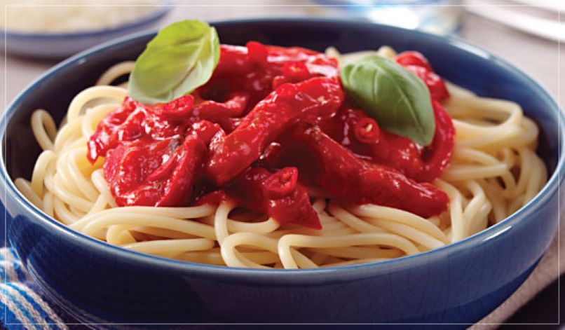 Blue bowl with spaghetti in and red sauce topped with two basil leaves