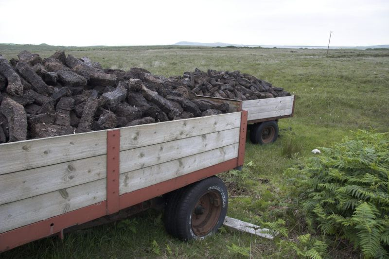 peat mining with pead on wooden cart in scotland