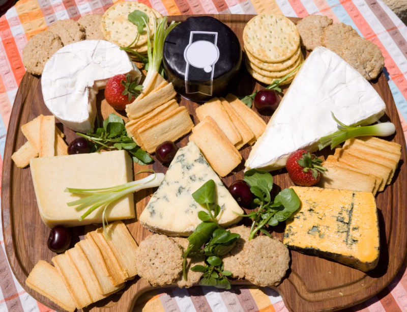 Assortment of different types of cheese on a board.