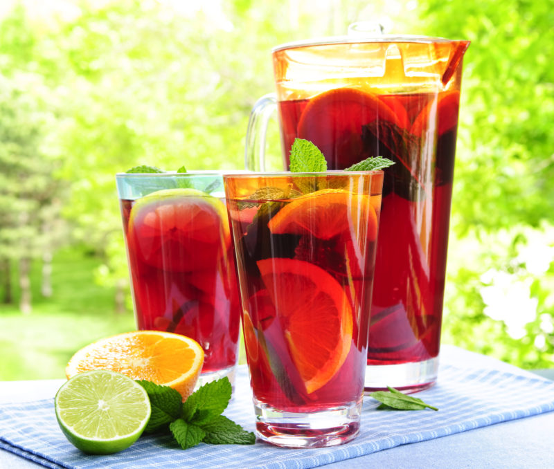 Fruit punch inside a pitcher and two glasses served with lemon and lime wedges.