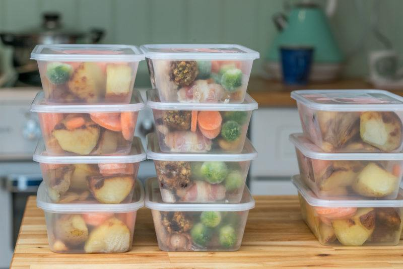 plastic containers with frozen fruits, meats, and vegetables with same ingredients for meal prepping