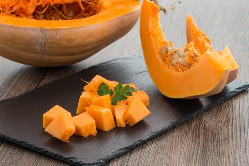 closeup image of an open pumpkin with a couple of slices and cubed pumpkin on a chopping board
