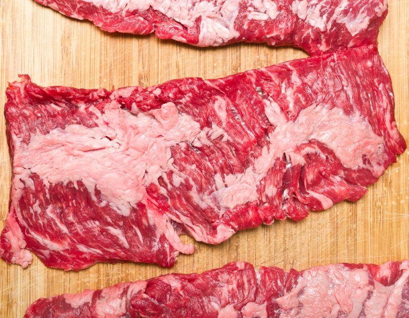 raw skirt steak on wooden cutting board