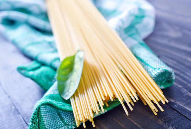 a closeup image of raw white pasta resting on top of a white and green table napkin, there is also a single herb on top of the pasta