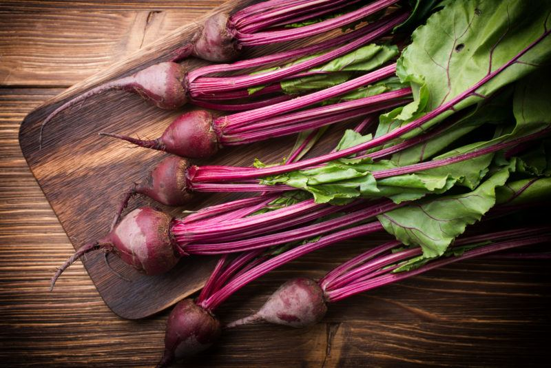 red beets with their stems on a wooden chopping board
