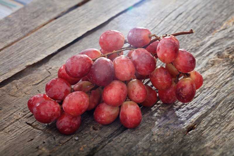 on a rustic wooden surface is a closeup image of a bunch of red grapes