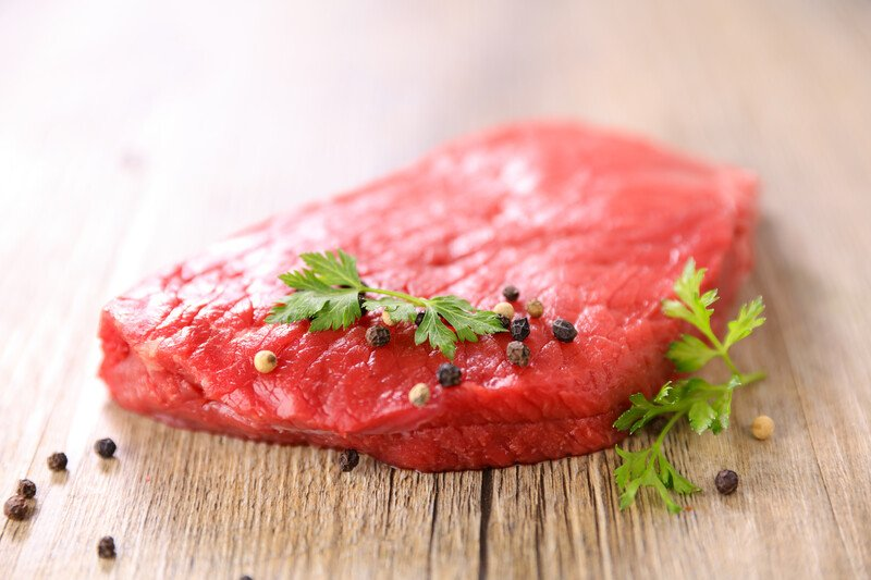 on a wooden surface is a big piece of red meat with herbs and spices on top and around it