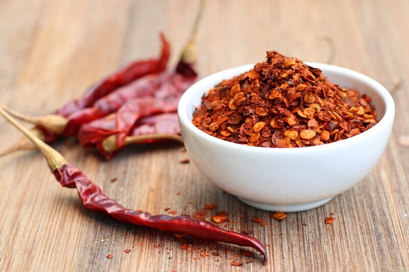 on a wooden surface is a white bowl full of red pepper flakes with loose pepper flakes and dried cayenne pepper around it
