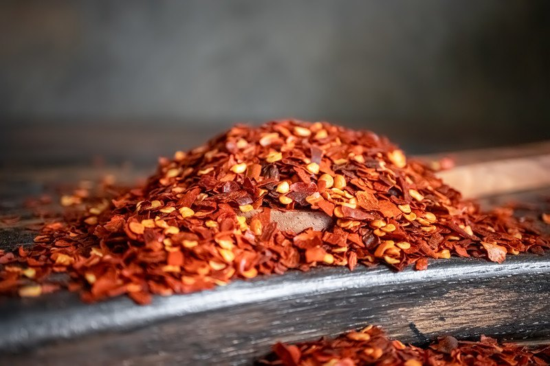 closeup image of a black wooden surface with a mound of red pepper flakes