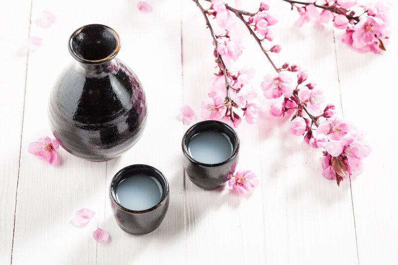 Black clay sake set with two cups and carage sitting on a white wood table with unfilitered sake in the glasses and cherry blossoms scattered around the set