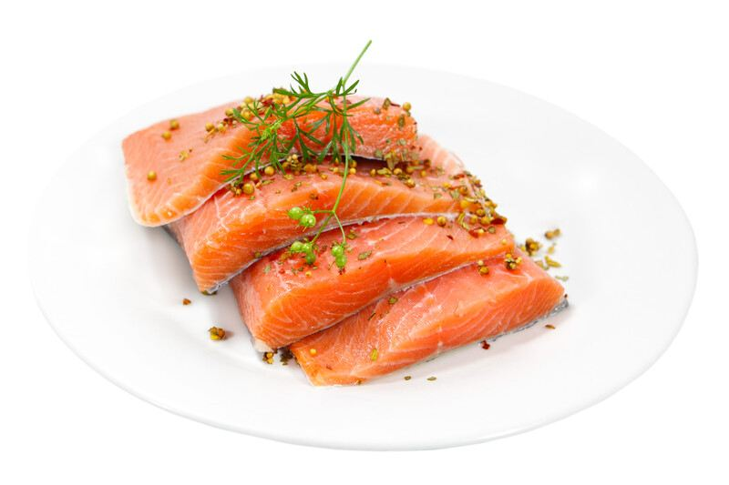Four raw salmon fillets garnished with herbs lie on a white plate against a white background.