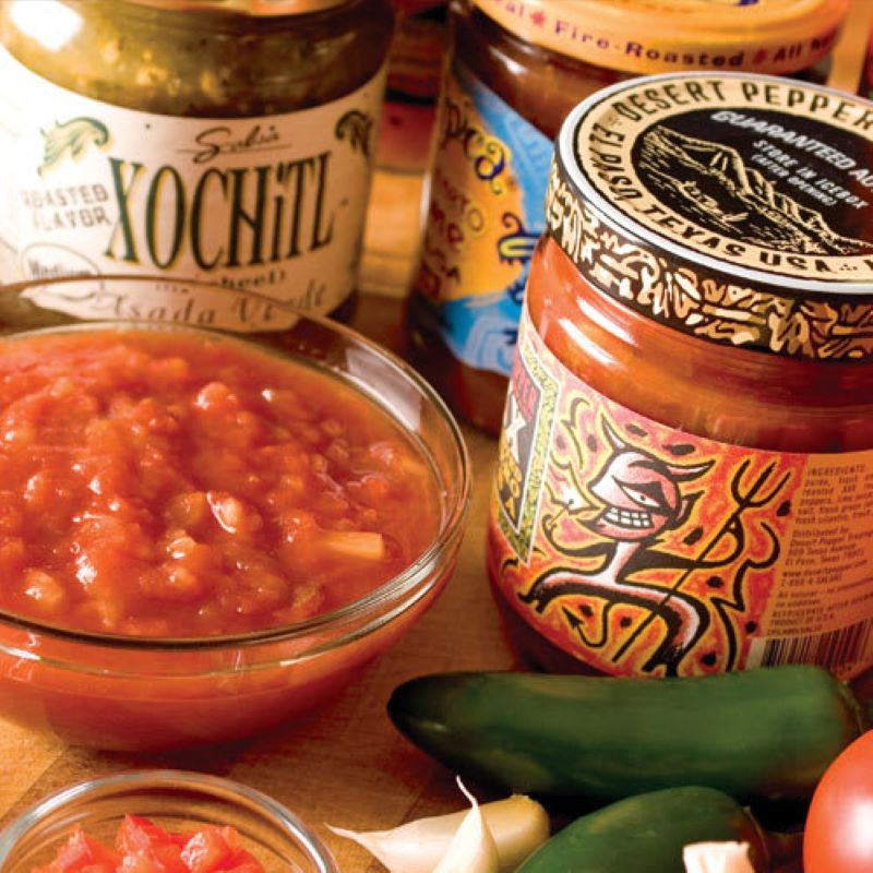 Close up of a small glass bowl of salsa with three jars of various brands in the background, in the right bottom corner are fresh jalapeno, tomato and garlic