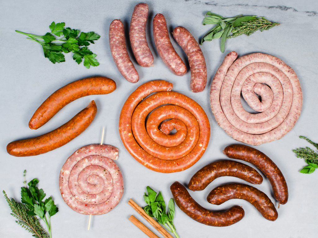 Variety of cooked and raw sausage links on a marble table, with fresh herbs scattered around the sausage.