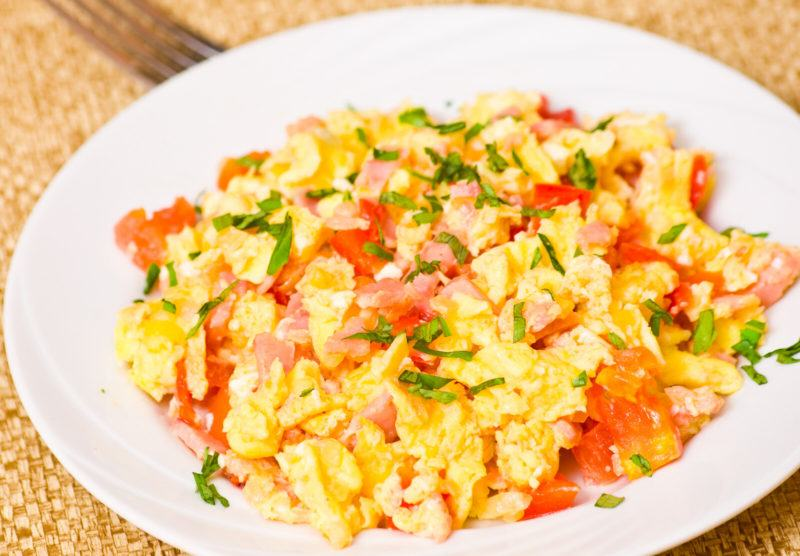scrambled eggs with basil, tomatoes, and ham on a white plate