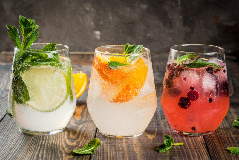 Three glasses of gin and tonic with different flavor combinations