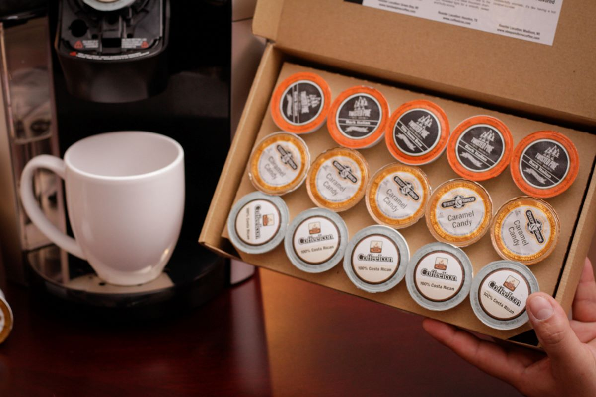 open Box of 15 single-serve coffee pods being held up with a single serve coffee maker in the background