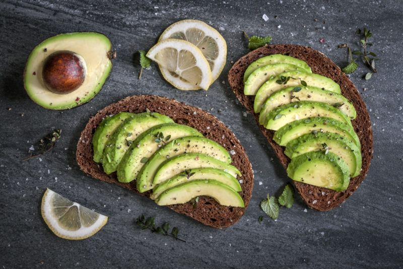 sliced avocado arranged neatly on two pieces of toasted rye bread.