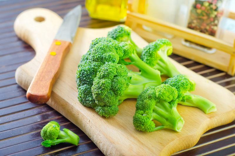 fresh broccoli florets and a small knife on top of a wood chopping board