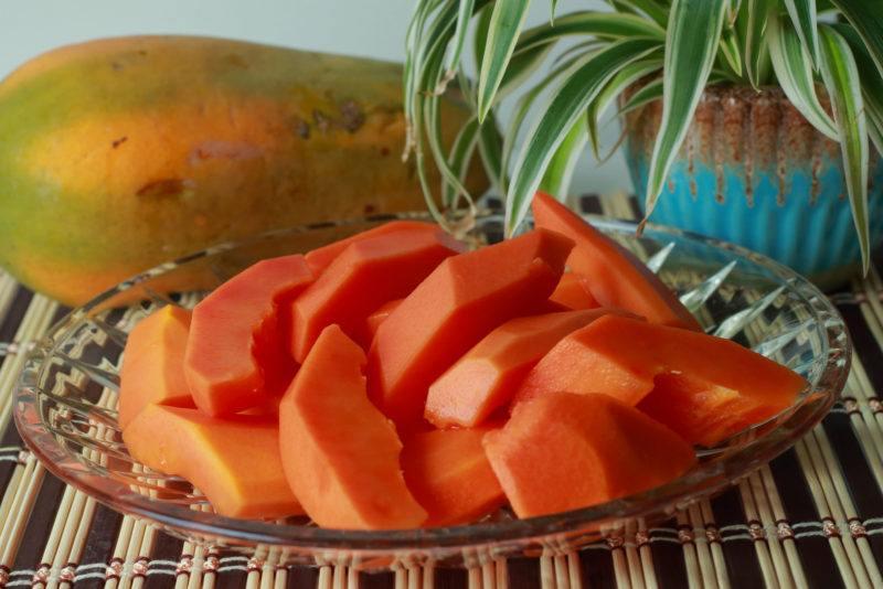a whole papaya and sliced papaya on a clear glass plate