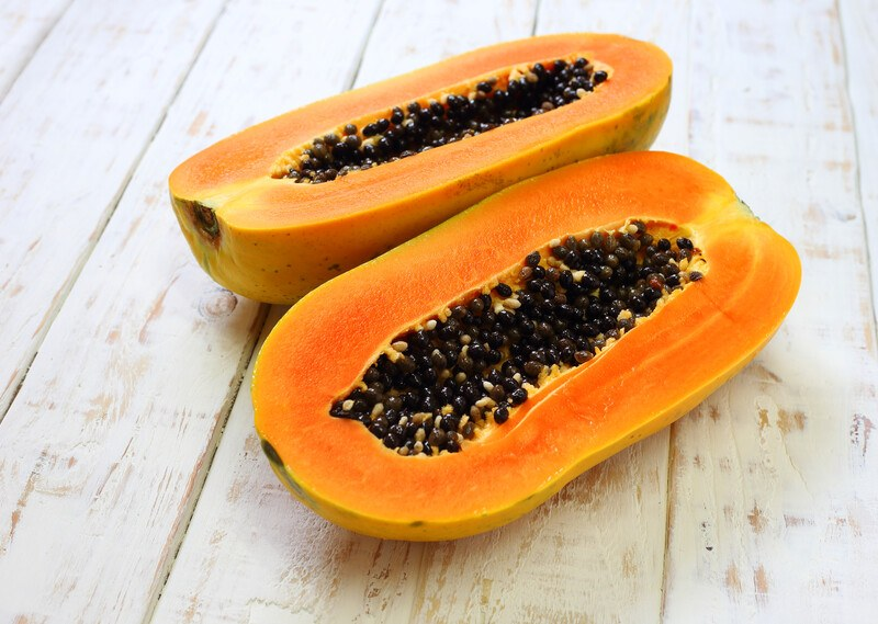 on a white wooden surface is a fresh papaya cut in half exposing its yellow flesh and black seeds