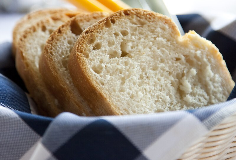 closeup image of slices of white bread in a basket lined with white and blue table napkin