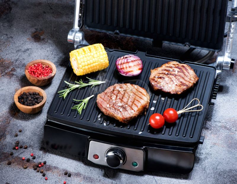 steak and vegetables on black indoor grill with non-stick ceramic grates