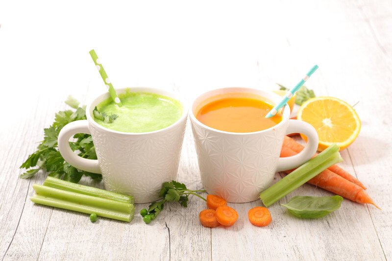 on a white wooden surface is a couple of white cup full of green and orange strained vegetable juice, with fresh vegetables around it