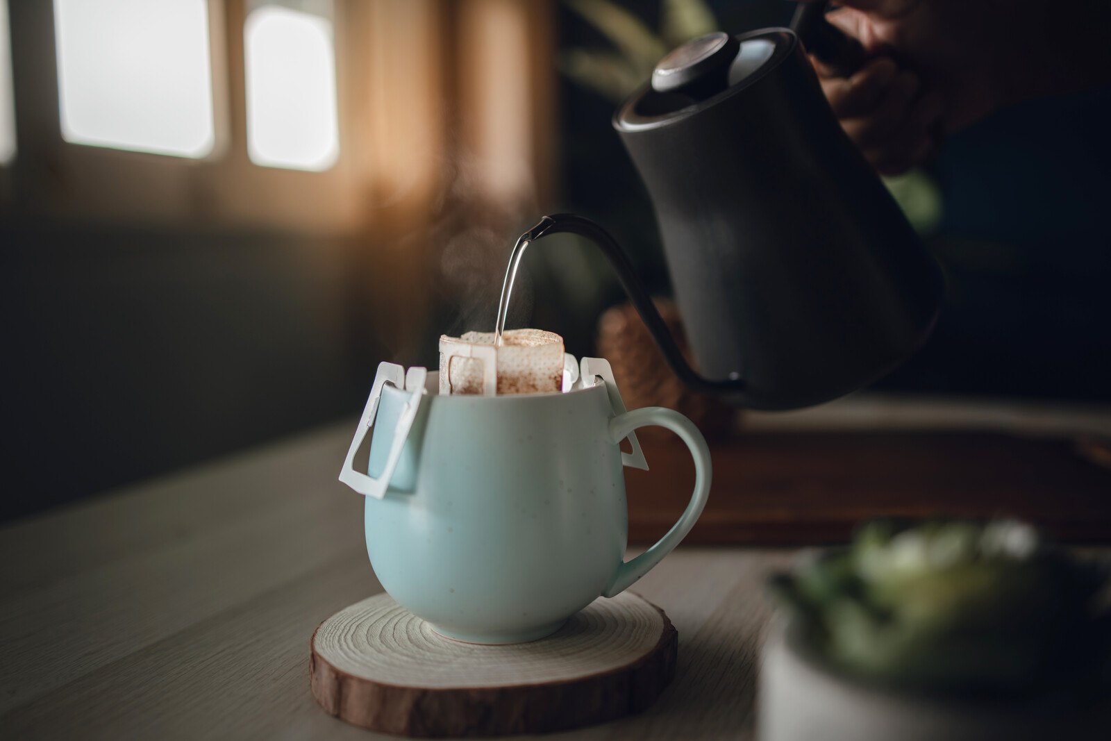 stylish black gooseneck kettle slowly pouring boiling water on a white coffee cup amid the morning light
