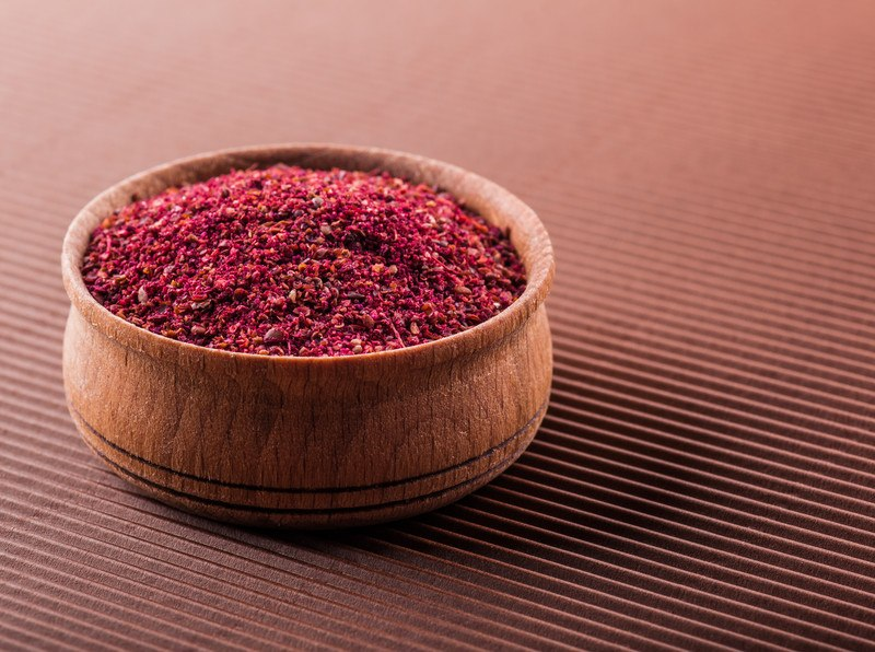 on a red surface is a wooden bowl full of sumac