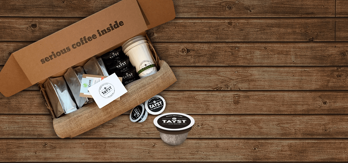 Box of Tayst coffee pods the box states in black ink Serious coffee inside.  The bbox contains various bags of coffee, recycleable coffee cups and business card with coffee pods displayed in front on a wood table