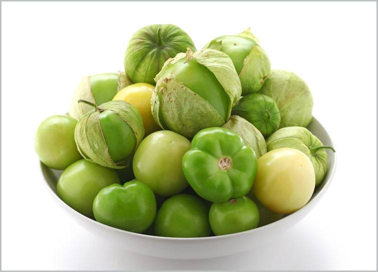 a closeup image of a white bowl full of tomatillos, a few still with husk