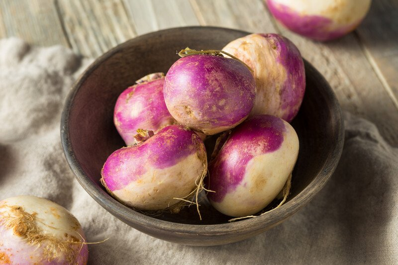 a closeup image of a wooden bowl full of turnips, resting on a wooden table