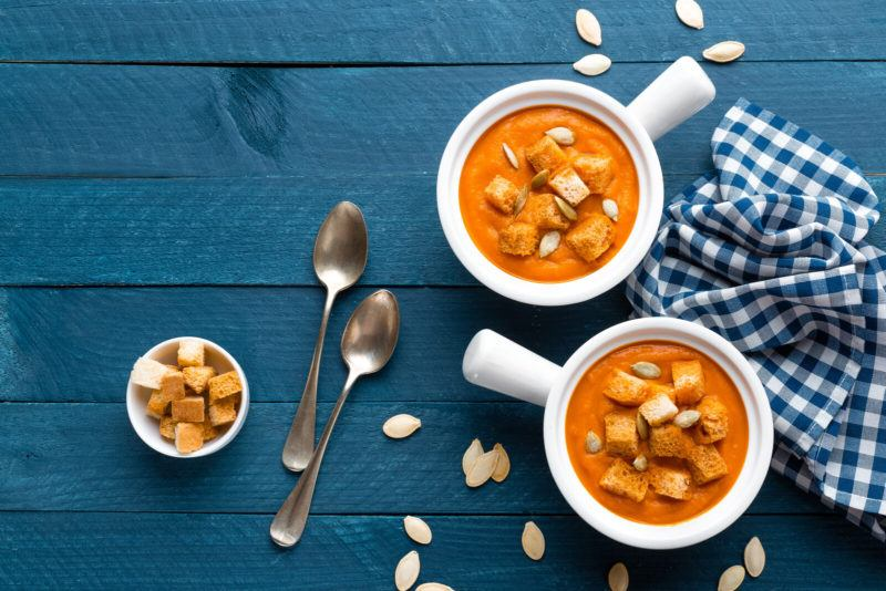 two bowls of pumpkin soup topped with croutons, on a blue table