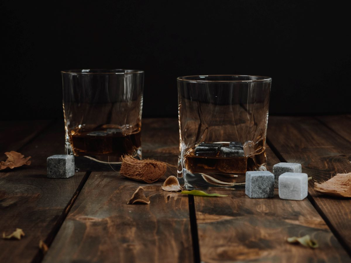 Rum of the Month Clubs - Two clear low ball glasses with rum and whiskey stones sitting on a dark wood table with scattered leaves
