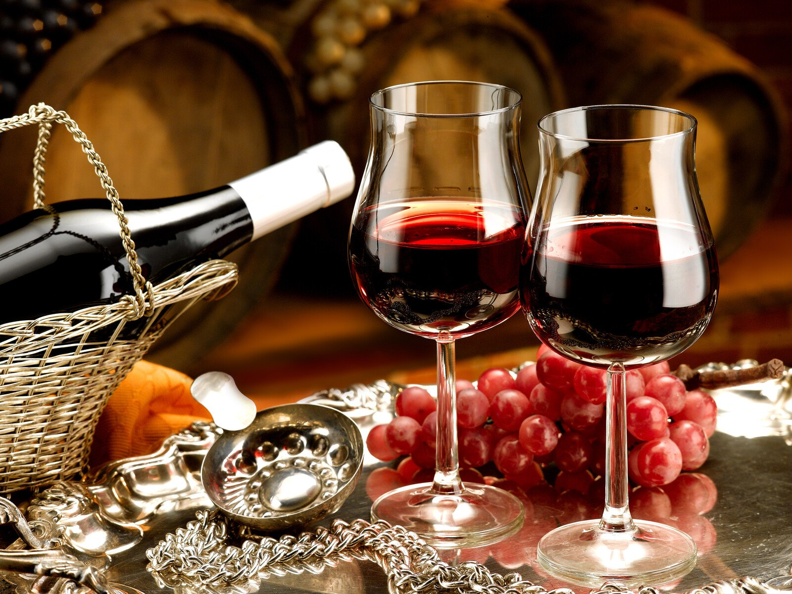 two glasses of red wine surrounded by a wine bottle lying on a wicker basket , a bunch of grapes and silverware