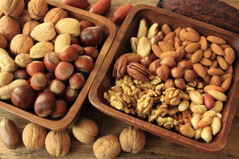peanuts, hazel nuts, macadamia nuts in wooden bowls