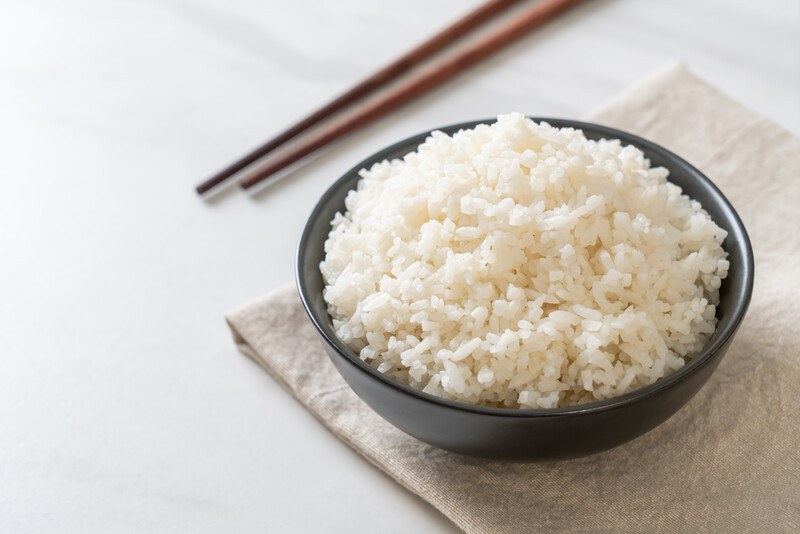 on a white surface is a black bowl full of cooked white rice, resting on a light brown table napkin with chopsticks at the back