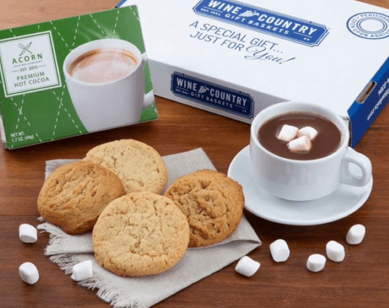 Wine and Country hot cocoa gift set with acorn bakery cookie box with four cookies sitting on a napkin and a white mug and saucer with hot cocoa in it, plus mini marshmallows in the cup and scattered on the table
