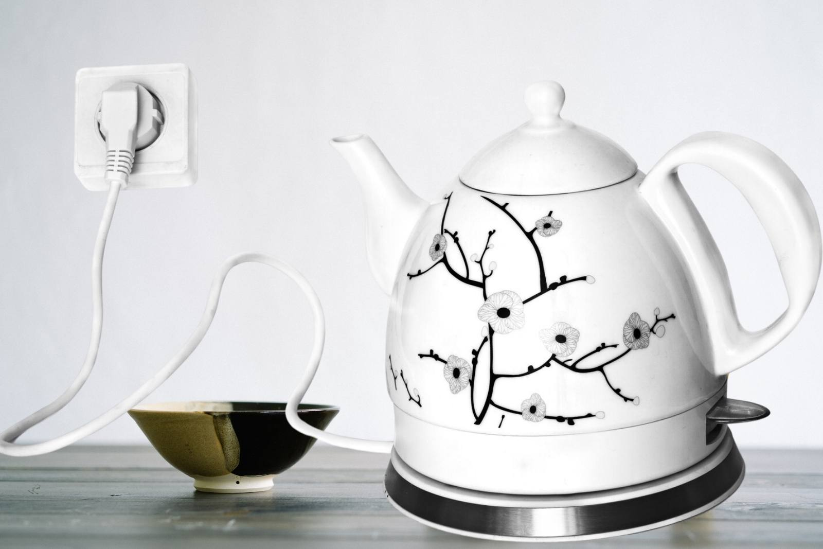 Porcelain electric teapot -with ceramic bowl on a dark brown table and white background